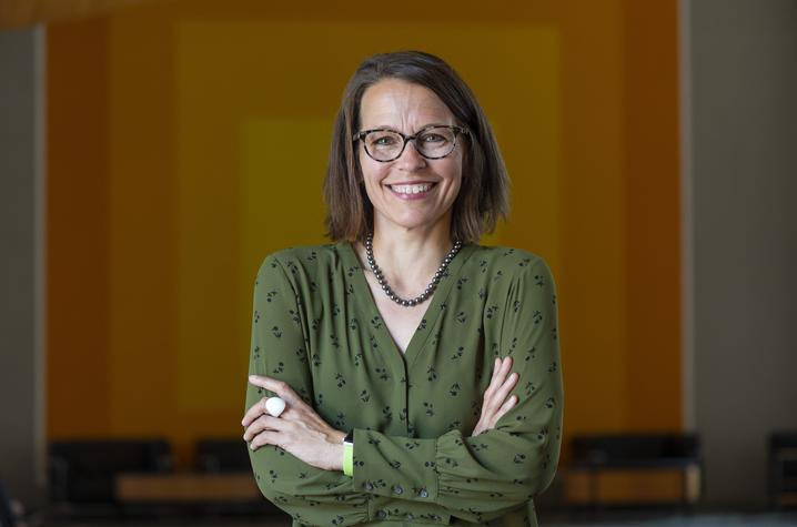 Author Juilee Decker in green shirt with glasses on wood background