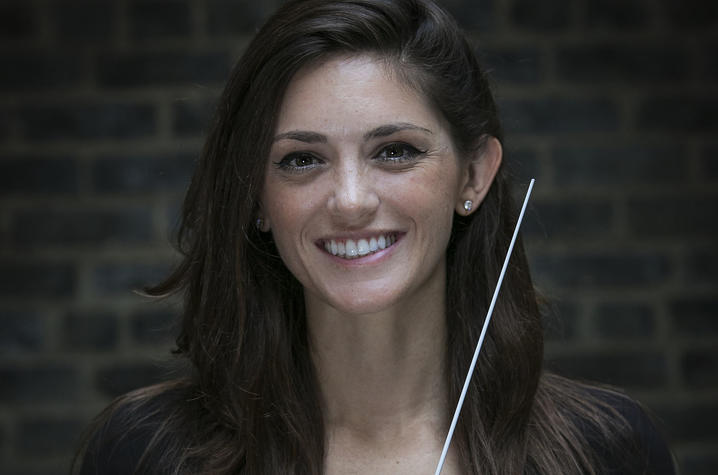 headshot photo of Kaitlin Bove with conducting baton