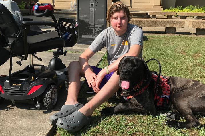 Kayne and service dog Moose on the quad at LSU