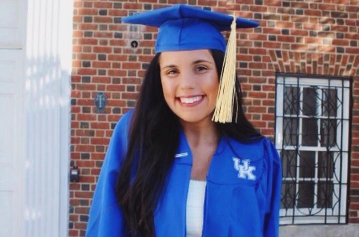photo of Kellie Patrick in cap and gown outside Memorial Hall