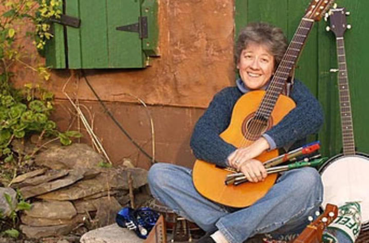 photo of LIza DiSavino leaning at door of house hugging her guitar surrounded by instruments