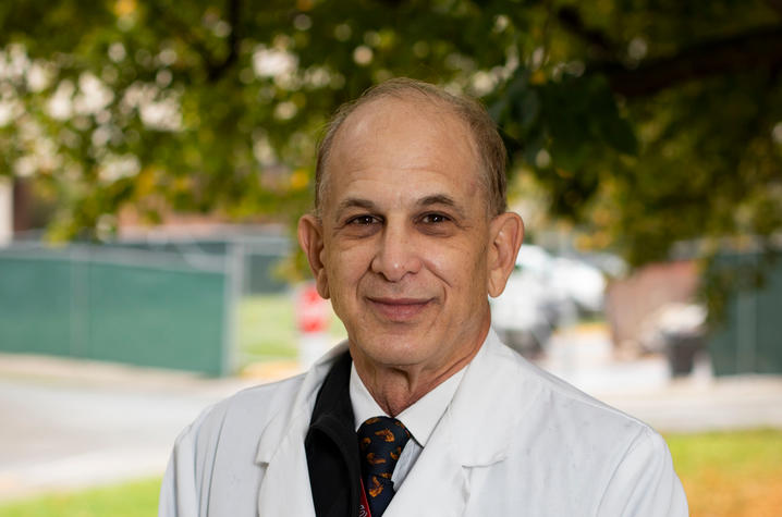 Dr. Richard Greenberg stands outside wearing his white coat. There is a tree behind him and colorful fallen leaves on the ground.