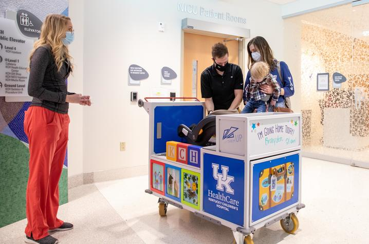 Photo of family trying out the NICU transport cart
