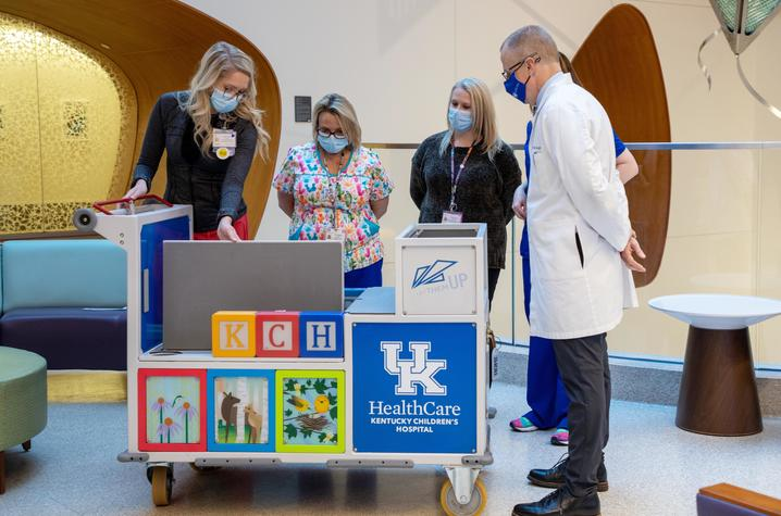 Image of KCH staff looking at transport cart
