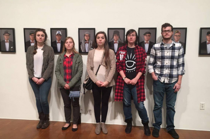 "photo of operations team from ""Art Entrepreneurship"" class with portraits from ""Saving Myself"" by Louis Zoellar Bickett"