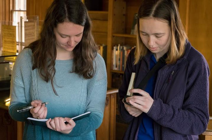 photo of Ali Bertelsman and Hannah Hatch taking notes