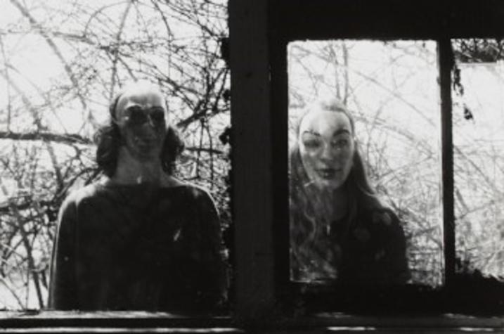 black and white photo of 2 adults in masks in window by Ralph Eugene Meatyard