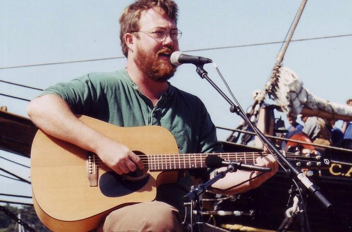 photo of Revell Carr with guitar at microphone singing sea chanteys in front of ship
