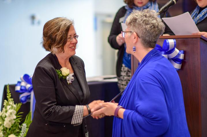 Women's Forum Chair C. Lynn Hiler, right, presents award to Lisa Collins.