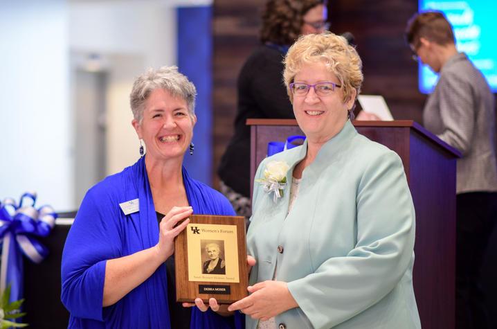 Women's Forum Chair C. Lynn Hiler, left, presents award to Debra Moser.