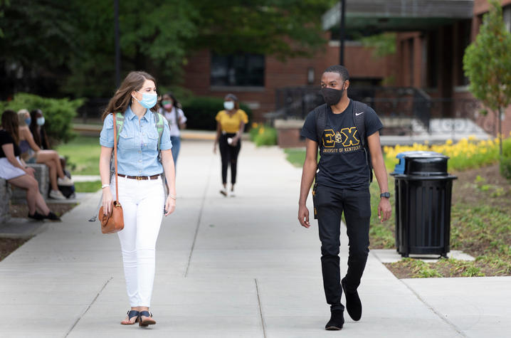 students with masks walking on campus