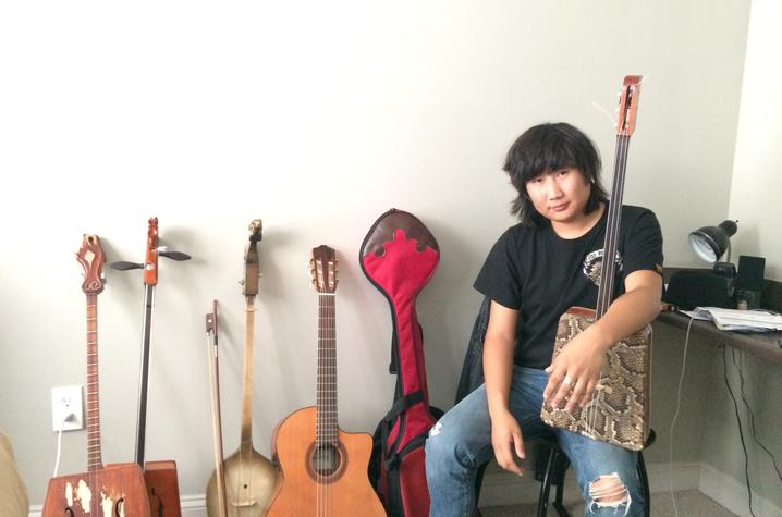 photo of Tamir Hargana seated by instruments and holding one