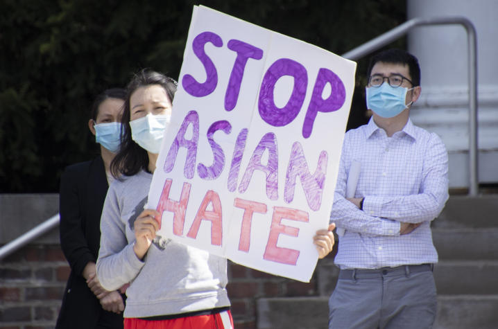 """photo of rally organizer Tracy Lu with sign that says """"Stop Asian Hate"""""""
