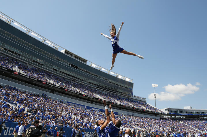 photo of a cheerleader being thrown in the air at a football game at Kroger Field