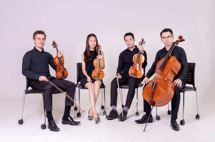 photo of Verdi Quartet seated in black chairs with string instruments with a white background