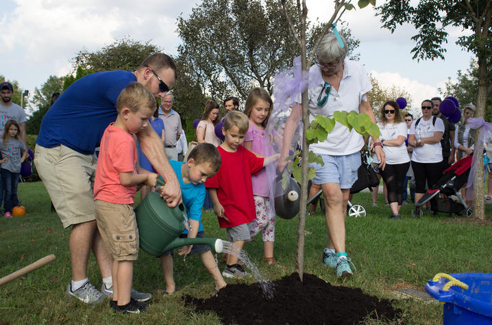photo of children planting and watering a tree
