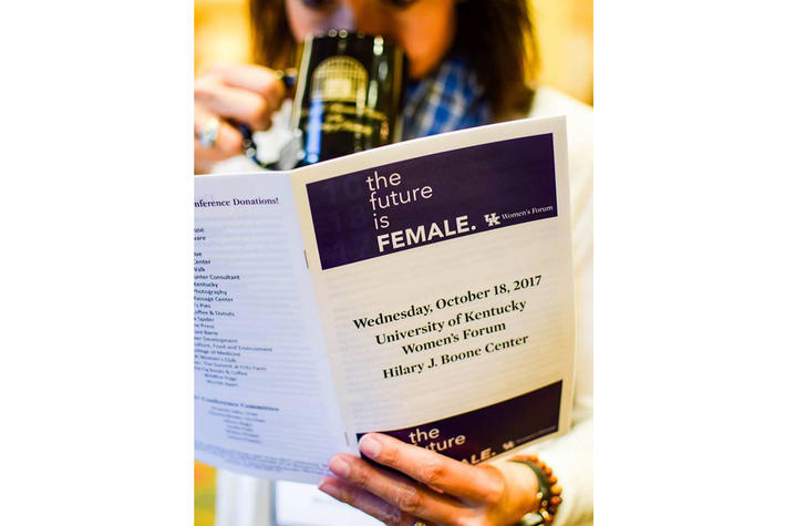 photo of woman looking at program from 2017 Women's Forum conference