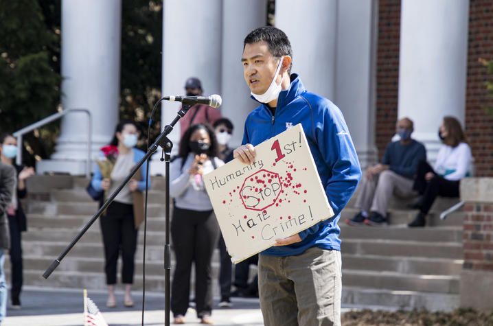 Yan Xia speaks at rally in front of Memorial Hall where others are sitting on the steps