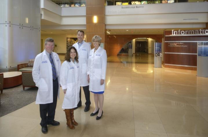 Four people standing in atrium