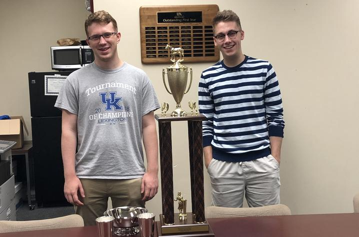 two guys standing with a trophy