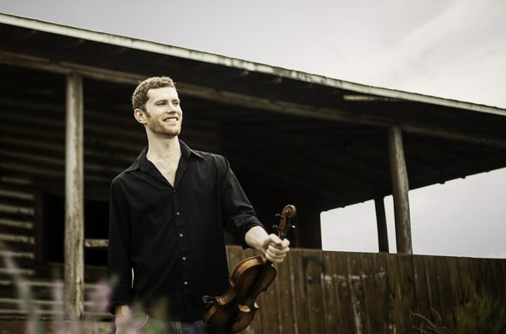 photo of Andrew Finn Magill outside cabin holding fiddle