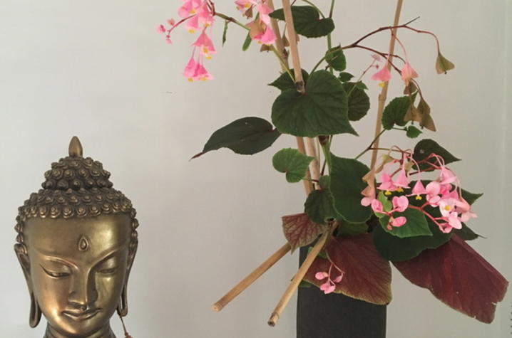 photo of Buddha bust and Asian-inspirec flower arrangement with bamboo