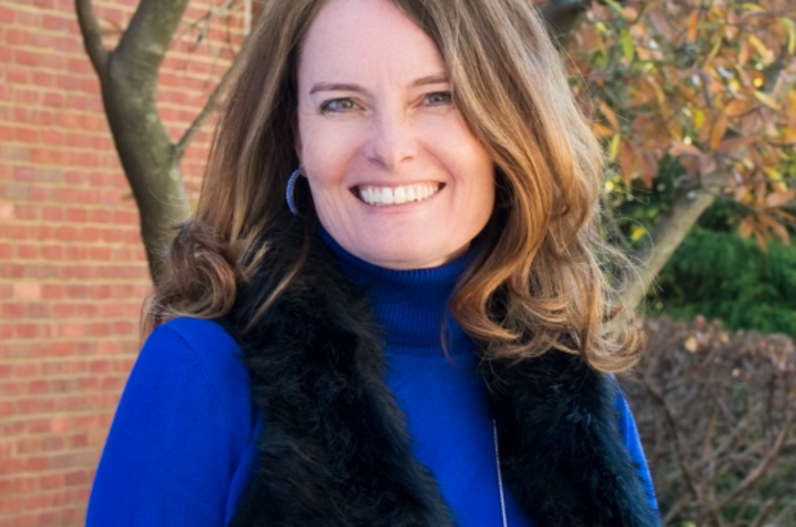 Erin N. Haynes, DrPH, MS, pictured in front of a brick building and tree with fall leaves. She wears a blue turtle neck and a black vest. Her light brown hair is shoulder length and she's smiling at the camera.
