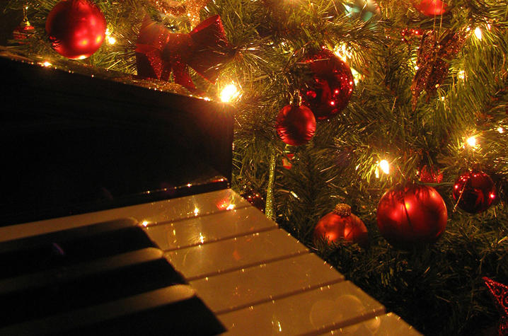 photo of Christmas tree with red ornaments and musical symbols next to piano