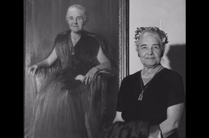 photo of Sarah Bennett Holmes standing beside her portrait.