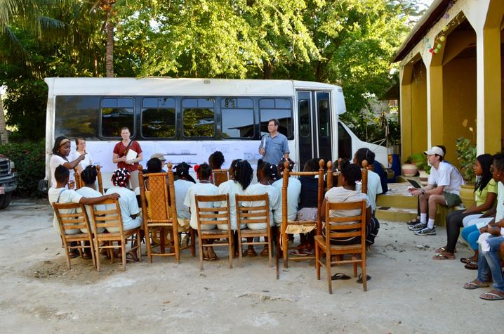 photo of students and Bruce Swetnam presenting plans for Haiti orphanage