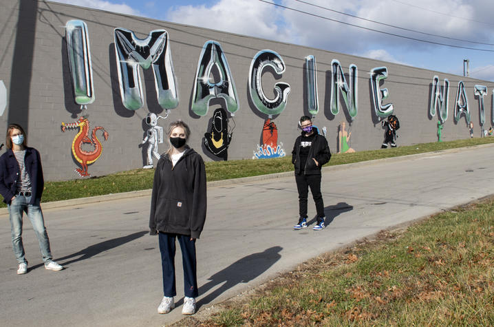"""photo of 3 Guerilla Art students with """"Imagine Nation"""" mural"""