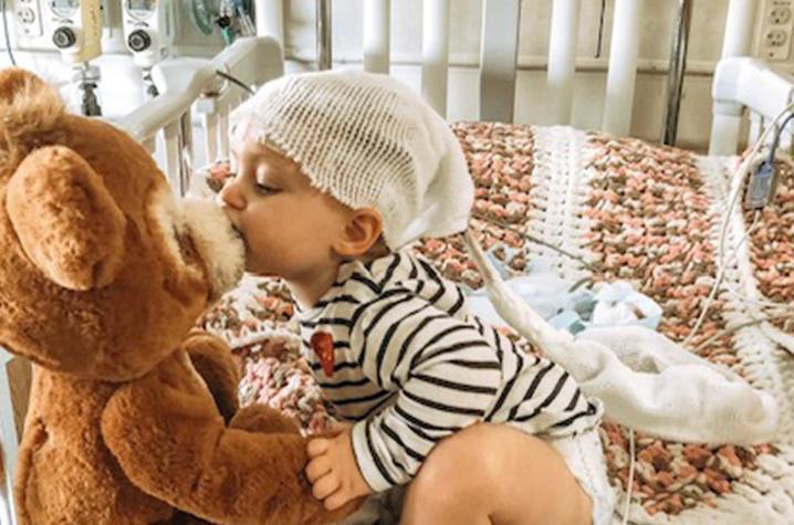 photo of Jaidyn with teddy bear in hospital bed