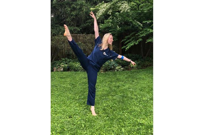 photo of Katelyn Cox dancing in scrubs in yard