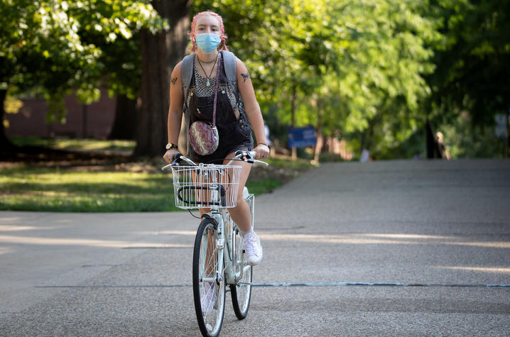 female student wearing mask bicycling on campus during covid pandemic