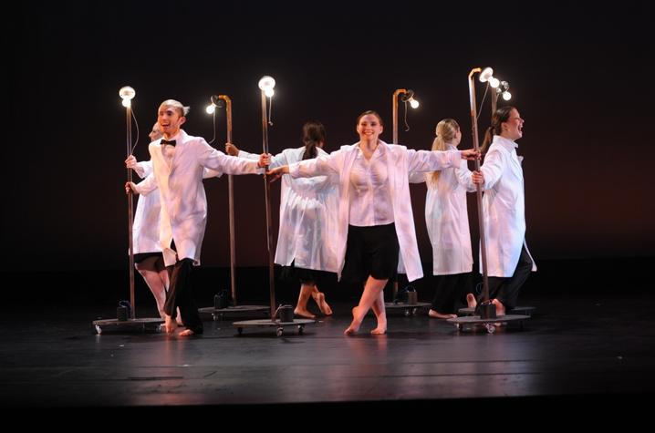 """photo of circle of 6 dancers (including Alyssa Noell Conley) in white coats with light bulbs performing """"Always Carry a Light Bulb"""""""