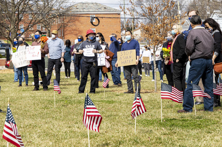 Rally attendees holding signs in front of American flags on lawn in front of Memorial Hall.