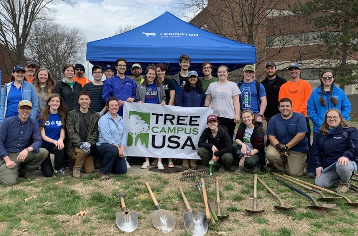 photo of group of people prior to a tree planting and a sign that says Tree Campus USA.