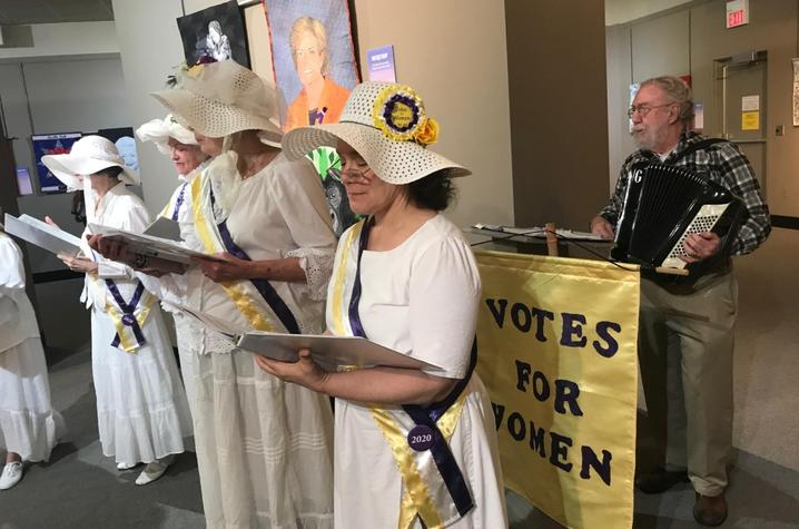 photo of 4 members of Women's Suffragist Centennial Chorus backed by man on accordian