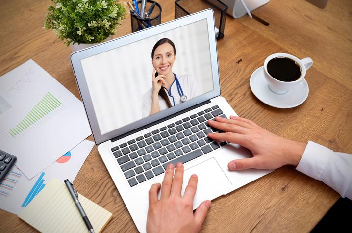 photo of man talking to doctor via computer