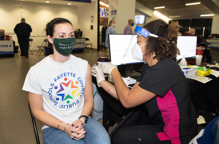 Teacher with Fayette County Public Schools T-shirt receives COVID-19 vaccine shot at Kroger Field vaccination clinic.