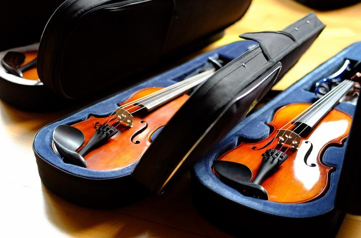 photo of 3 violin cases with violins on floor