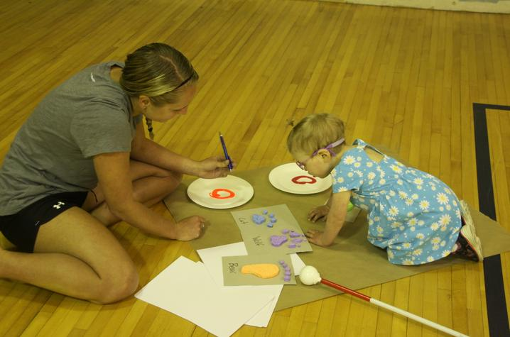 adult and child paint animal tracks on floor