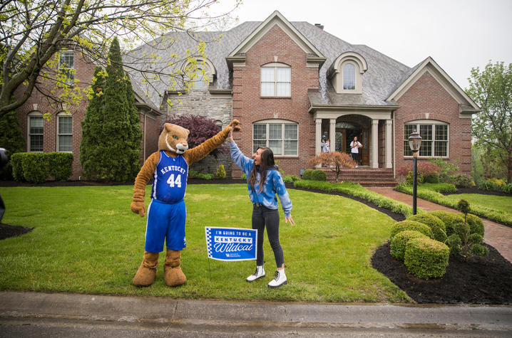 """Wildcat high fives with incoming freshman in her front yard with yard sign saying """"I'm going to be a Kentucky Wildcat"""""""