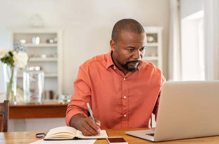 man working from home with laptop and phone