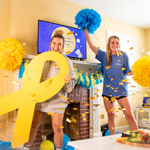 Two females with DanceBlue yellow ribbon, confetti and pompoms