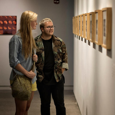 """photo of 2 students looking at David Wischer's work - """"Faculty Series: Vol. I"""""""
