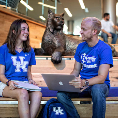 Two people sitting on the Student Center stairs.