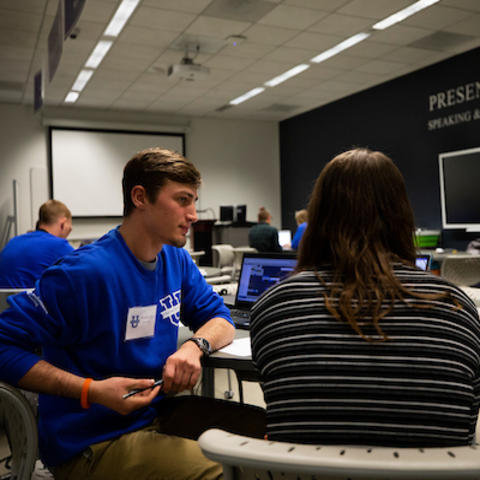 photo of student employee at PresentationU working with another student