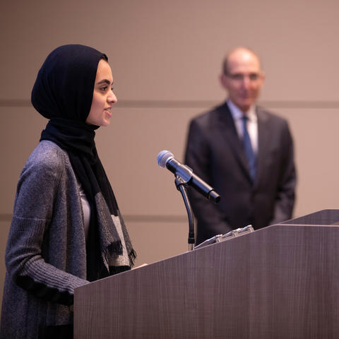 photo of Hadeel Abdallah speaking at BOT meeting with President Capilouto in background