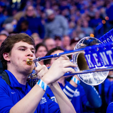 photo of John Schulz with blue tiles spelling out Kentucky on trombone slide